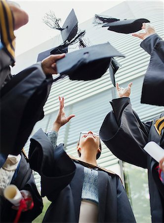 Students in gowns throwing caps in the air Stock Photo - Premium Royalty-Free, Code: 6113-07791489