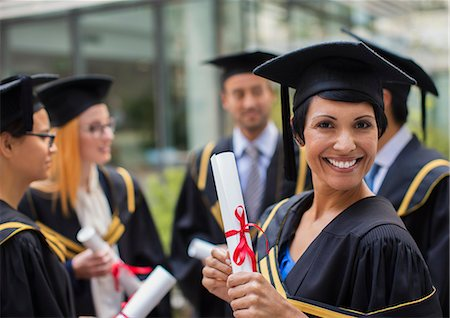 Student in cap and gown smiling with colleges Stock Photo - Premium Royalty-Free, Code: 6113-07791499