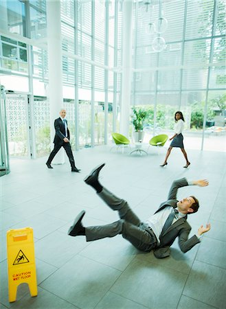 dangerous accident - Businessman slipping on floor of office building Stock Photo - Premium Royalty-Free, Code: 6113-07791401
