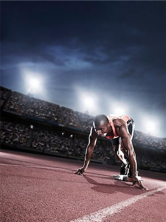 race track (people) - Runner poised at starting line on track Stock Photo - Premium Royalty-Free, Code: 6113-07730488