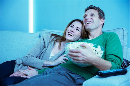 Couple watching television on sofa Stock Photo - Premium Royalty-Free, Code: 6113-07730543