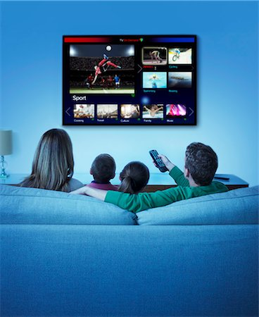 Family watching television in living room Stock Photo - Premium Royalty-Free, Code: 6113-07730545