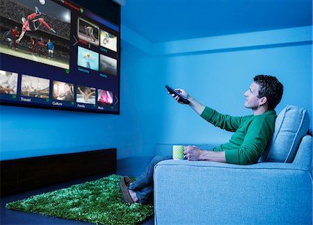 Man watching television in living room Stock Photo - Premium Royalty-Free, Code: 6113-07730551
