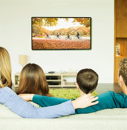 Family watching television in living room Stock Photo - Premium Royalty-Free, Code: 6113-07730556