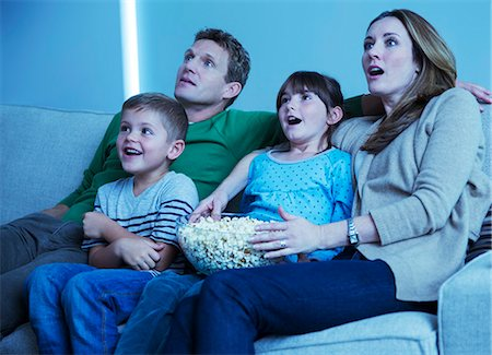 Family watching television in living room Stock Photo - Premium Royalty-Free, Code: 6113-07730564