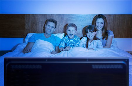 Family watching television in bed Stock Photo - Premium Royalty-Free, Code: 6113-07730573
