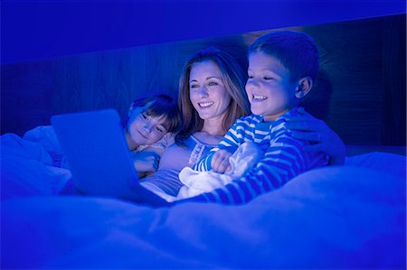 Mother and children using digital tablet in bed Stock Photo - Premium Royalty-Free, Code: 6113-07730570