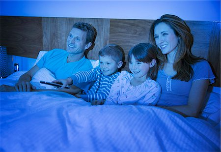 Family watching television in bed Stock Photo - Premium Royalty-Free, Code: 6113-07730575