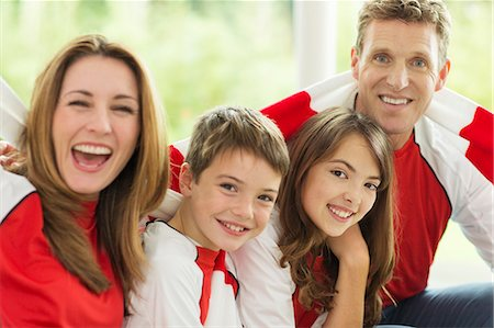 Family in sports jerseys cheering in living room Stock Photo - Premium Royalty-Free, Code: 6113-07730576