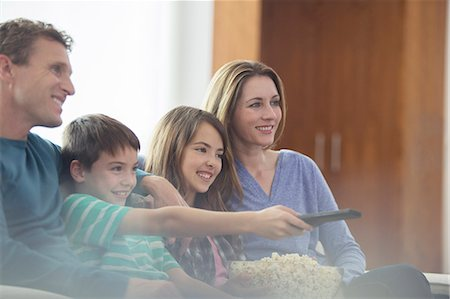 Family watching television in living room Stock Photo - Premium Royalty-Free, Code: 6113-07730588