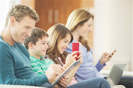 Family using technology on sofa Stock Photo - Premium Royalty-Free, Code: 6113-07730508