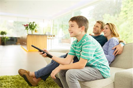 Family watching television in living room Stock Photo - Premium Royalty-Free, Code: 6113-07730513