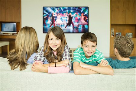 Family watching television in living room Stock Photo - Premium Royalty-Free, Code: 6113-07730518