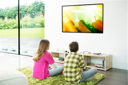 Children watching television in living room Stock Photo - Premium Royalty-Free, Code: 6113-07730526