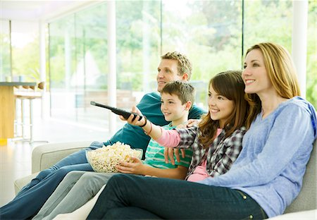 Family watching television in living room Stock Photo - Premium Royalty-Free, Code: 6113-07730528