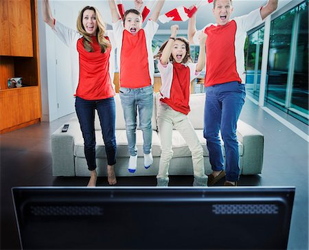 Family cheering in front of television in living room Stock Photo - Premium Royalty-Free, Code: 6113-07730532