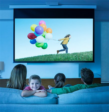 Family watching television in living room Stock Photo - Premium Royalty-Free, Code: 6113-07730535