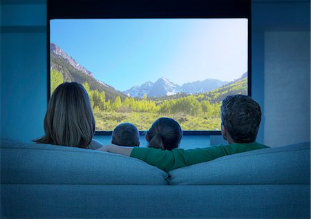Family watching television in living room Stock Photo - Premium Royalty-Free, Code: 6113-07730538