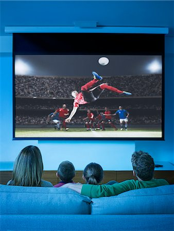 Family watching television in living room Stock Photo - Premium Royalty-Free, Code: 6113-07730539
