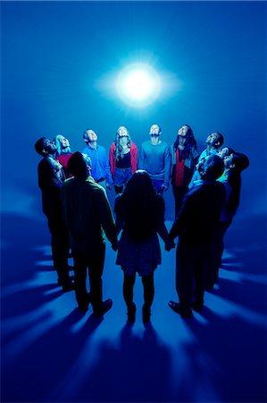 Group basking around bright light Stock Photo - Premium Royalty-Free, Code: 6113-07730651