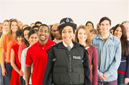 female police officer happy - Portrait of smiling policewoman in front of large crowd Stock Photo - Premium Royalty-Free, Code: 6113-07730656