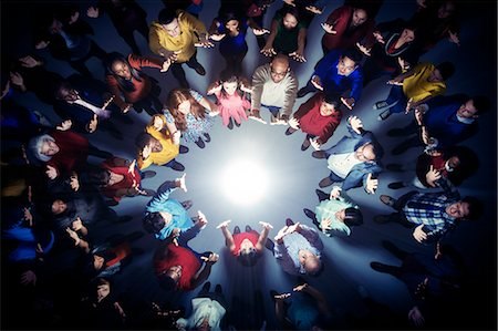 Business people forming circle around bright light Stock Photo - Premium Royalty-Free, Code: 6113-07730693