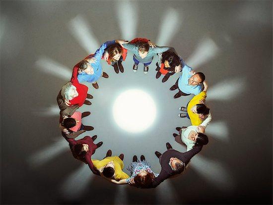 Diverse group around bright light Stock Photo - Premium Royalty-Free, Image code: 6113-07730637
