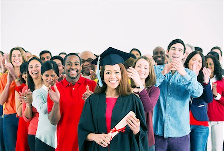 Crowd clapping behind happy graduate Stock Photo - Premium Royalty-Free, Code: 6113-07730639