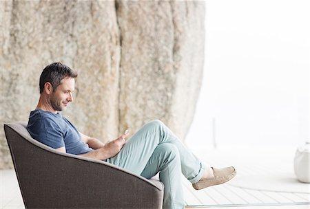 rich lifestyle - Man sitting in modern armchair Stock Photo - Premium Royalty-Free, Code: 6113-07730767