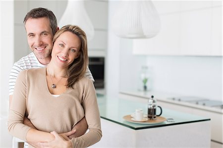 property release - Couple hugging in modern kitchen Stock Photo - Premium Royalty-Free, Code: 6113-07730786