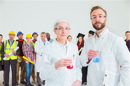 Portrait of scientists with workforce in background Stock Photo - Premium Royalty-Free, Code: 6113-07730720