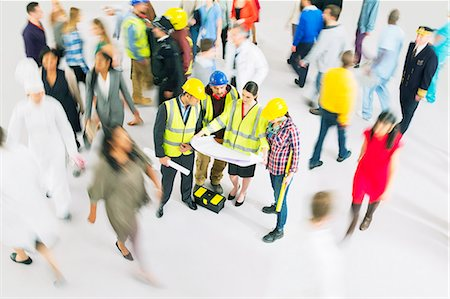 Construction workers viewing blueprints among crowd Stock Photo - Premium Royalty-Free, Code: 6113-07730735