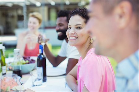 Woman smiling at table outdoors Stock Photo - Premium Royalty-Free, Code: 6113-07730861