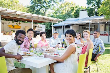 Friends smiling at table outdoors Stock Photo - Premium Royalty-Free, Code: 6113-07730934