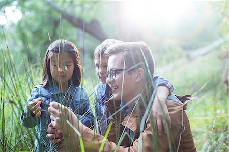 Students and teacher examining grass in forest Stock Photo - Premium Royalty-Free, Code: 6113-07731147