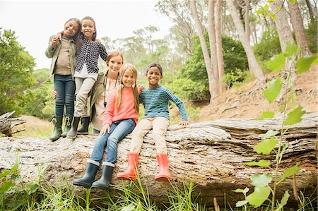 Students and teacher sitting on log in forest Stock Photo - Premium Royalty-Free, Code: 6113-07731157
