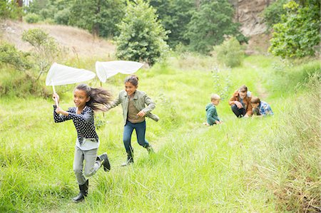 Children playing with butterfly nets on dirt path Stock Photo - Premium Royalty-Free, Code: 6113-07731160