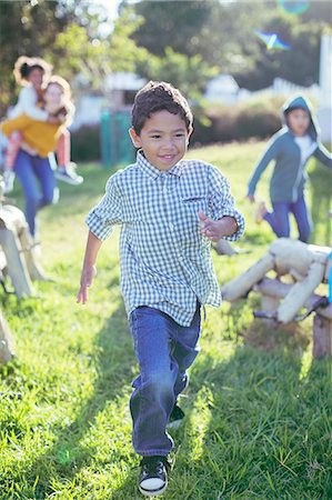 filipino ethnicity - Boy walking in grass outdoors Stock Photo - Premium Royalty-Free, Code: 6113-07731198