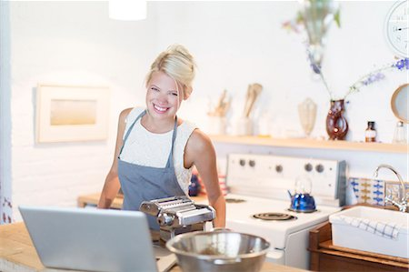 Woman at laptop cooking in kitchen Stock Photo - Premium Royalty-Free, Code: 6113-07731102