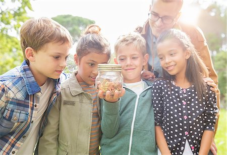 Student and teacher examining insects in jar outdoors Stock Photo - Premium Royalty-Free, Code: 6113-07731139