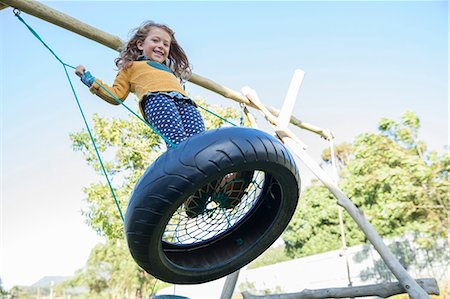 Girl playing on tire swing Stock Photo - Premium Royalty-Free, Code: 6113-07731257