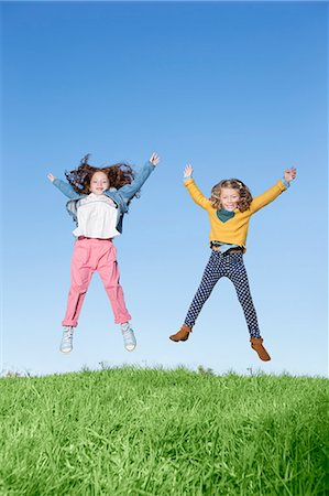 fall - Girls jumping for joy on grassy hill Stock Photo - Premium Royalty-Free, Code: 6113-07731285