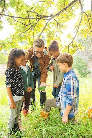 Students and teacher examining leaf outdoors Stock Photo - Premium Royalty-Free, Code: 6113-07731201