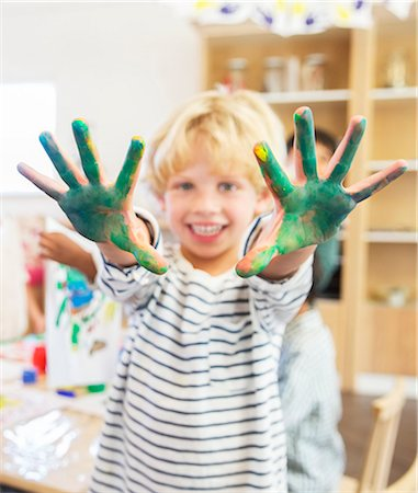 finger painting - Student showing off messy hands in classroom Stock Photo - Premium Royalty-Free, Code: 6113-07731211