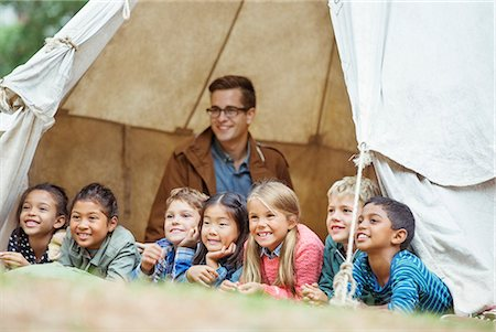 four - Students and teacher smiling in tent at campsite Stock Photo - Premium Royalty-Free, Code: 6113-07731311