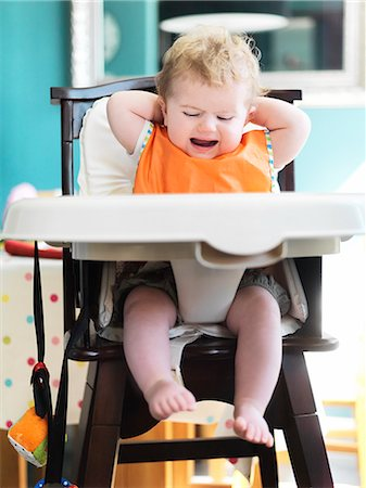 Baby girl crying in high chair Stock Photo - Premium Royalty-Free, Code: 6113-07731332