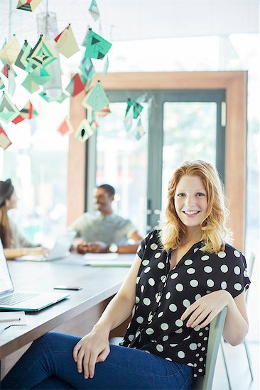 Woman smiling at conference table in office Stock Photo - Premium Royalty-Free, Image code: 6113-07731472