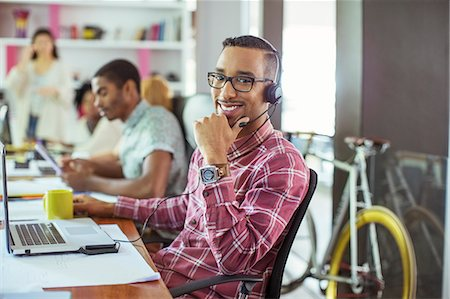 Man smiling at desk in office Stock Photo - Premium Royalty-Free, Code: 6113-07731406