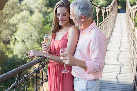 Couple toasting each other on wooden rope bridge Stock Photo - Premium Royalty-Free, Code: 6113-07731531