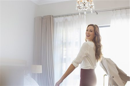 Businesswoman getting dressed in hotel room Stock Photo - Premium Royalty-Free, Code: 6113-07731643